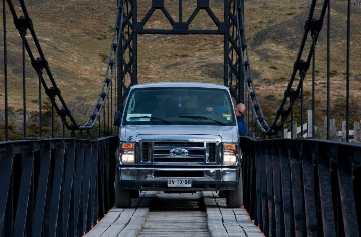 With his head out the window, a driver creeps across the Black Bridge with a load of clients.