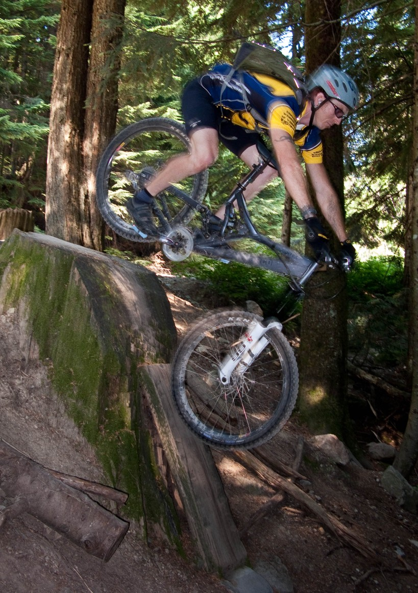 A guest rider making the stump drop on Upper Oil Can look easy