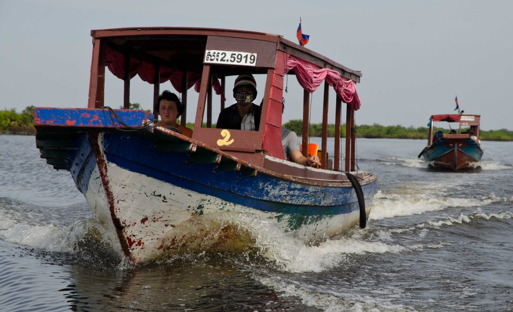 A long tail boat heads out onto Tonlé Sap Lake