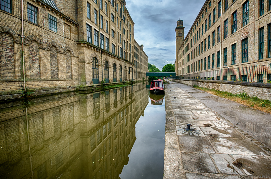 A canal runs between the factory buildings in Saltaire.