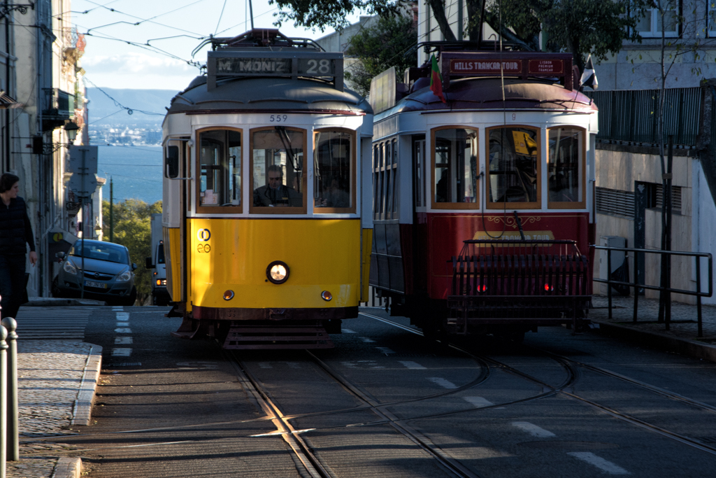 Tram 28 and the tourist tram pass each other in Lisbon.